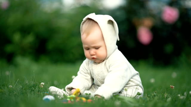 Cute little toddler baby playing in the park on grass at day time video