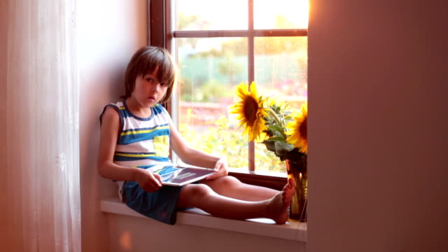 Cute little toddler child, playing on tablet on a window video