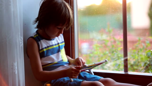 Cute little toddler child, playing with abacus on a window video