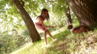 Cute Multi-ethnic girl playing sticks with her puppy in a park video