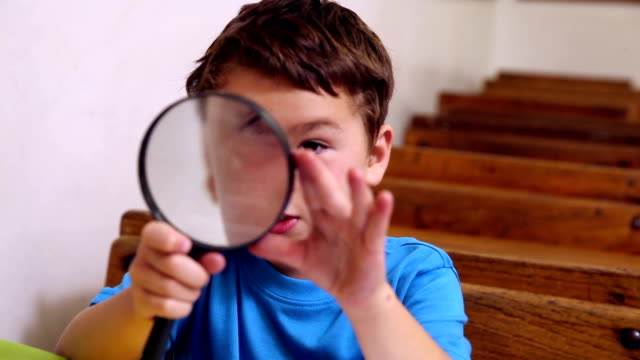 Cute pupil holding magnifying glass video