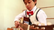 Cute pupil playing guitar in classroom video