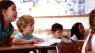 Cute pupils listening attentively in classroom video