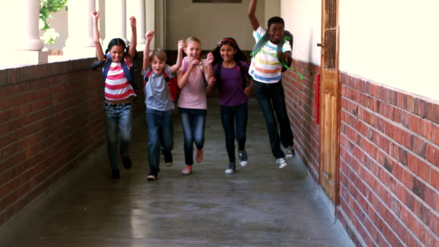 Cute pupils running and smiling at camera in hallway video