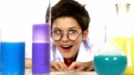Cute, sly little boy in uniform round glasses stands up and evaluates among chemical test tubes, on white background, slow motion video