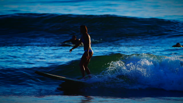 A cute surfer girl catches an ocean wave and rides it with grace and poise, showcasing femininity but with an edge of athleticism and grace. video