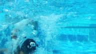 Cute teen girl dives in blue pool in the water video