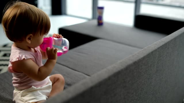 Cute toddler drinking water on the sofa video