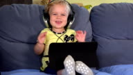 Cute toddler girl with headphones using tablet and listening to music video