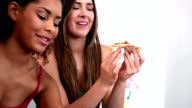 Cute women enjoying pizza sitting on couch video