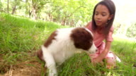 Cute young African-American long haired brunette girl cuddling a  puppy video