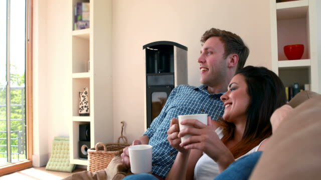 Cute young couple relaxing on the couch with coffee video