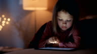 Cute Young Girl Lies in Her Bed with Laptop Computer. She Interacts with Device. Her Room is Cozy and Bed Lights are On. video