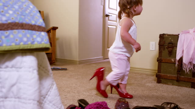 Cute young girl trying on mommy's shoes video