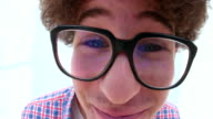 Cute young man with glasses making silly faces video