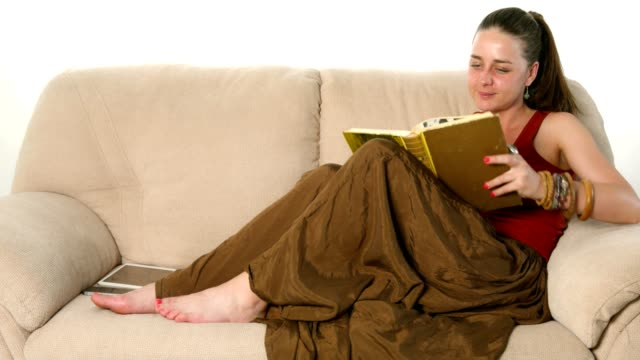 Cute young woman lying on the couch and reading a book video