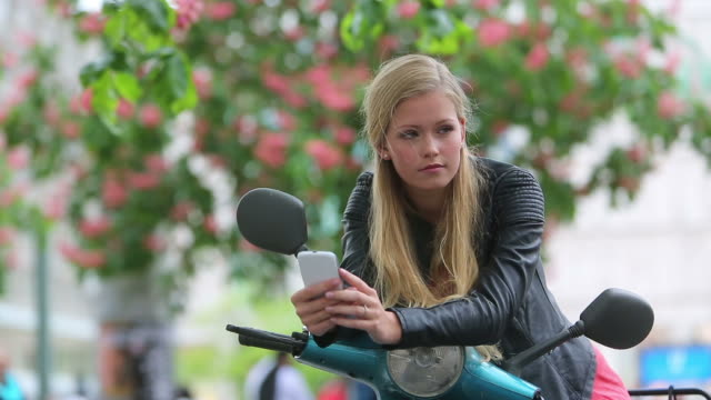 Cute young woman on a scooter looking at the cell phone video