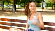 Cute young woman sitting on a bench in the park and listening to music played from her smart phone video