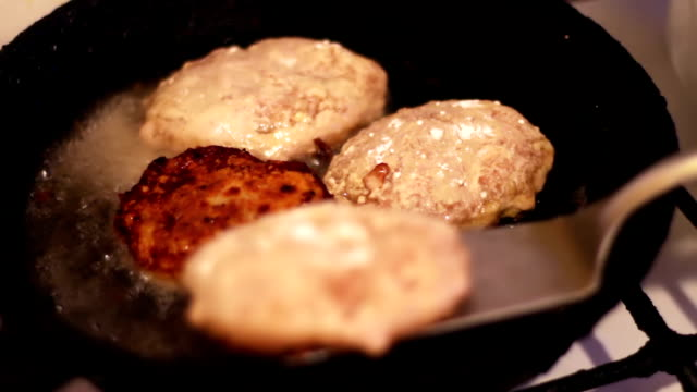Cutlets for hamburgers are fried in a frying pan in the home kitchen video