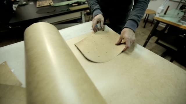Cuts cardboard frame for making handbags. video