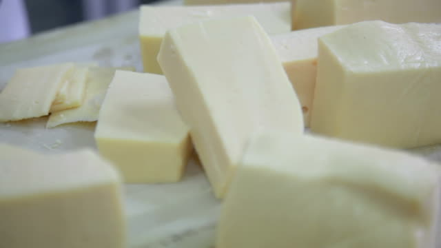 Cutting brick of cheese into slices video
