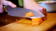 Cutting Carrots into Slices on Chopping Board in Home Kitchen. Slow Motion video