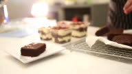 Cutting Chocolate Brownie Cake into slices and set on plate video
