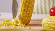 Cutting corn kernels of cob, closeup video