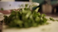 Cutting fresh organic parsley with knife on wooden cutting board. video
