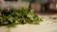 Cutting fresh organic parsley with knife on wooden cutting board. video