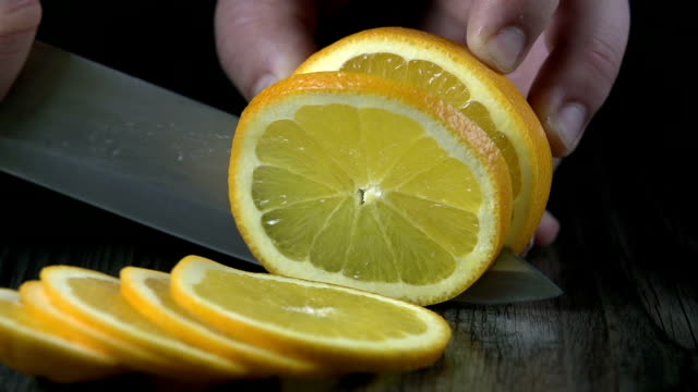 HD SLOW: Cutting lemon into thin pieces for making drink video