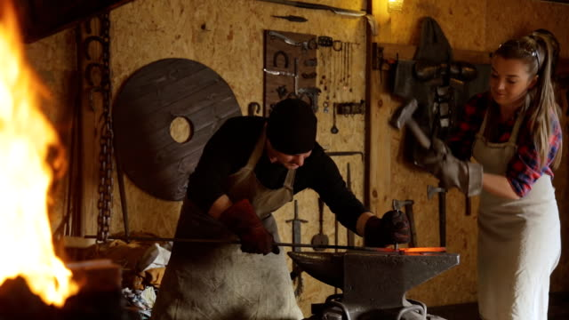 Cutting metal by hand forging with help of two people video