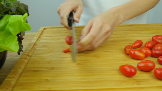 Cutting tomato on wooden table. video