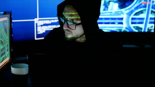 cyber security center filled with display screens, Male hacker working on computer, IT professional programmer in glasses is working on computer video