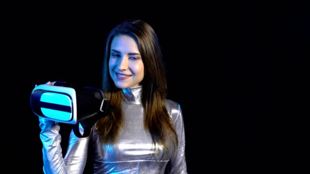 Cyber young woman in silver clothing showing virtual reality googles video