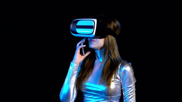 Cyber young woman in silver clothing wearing virtual reality googles video