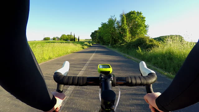 Cycling along a country road in the woods in springtime video