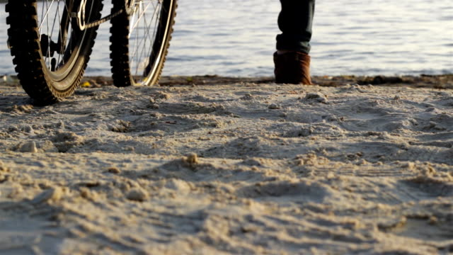 Cyclist comes to beach and sits enjoying the view video