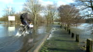 Cyclist passes through a flooded road video