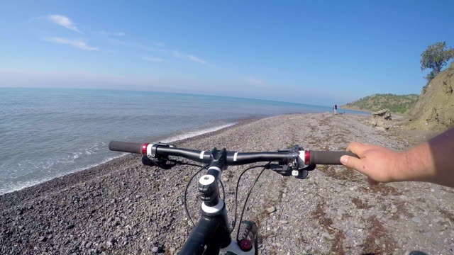 Cyclist Point of view Travelers pushing bikes along the wild pebble beach video