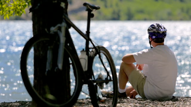 Cyclist Sits by Picturesque Lake video