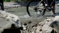 Cyclists crossing water stream pushing mountain bikes during cross country cycling in summer video