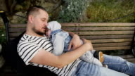 Dad and little son rest in the park on a bench video
