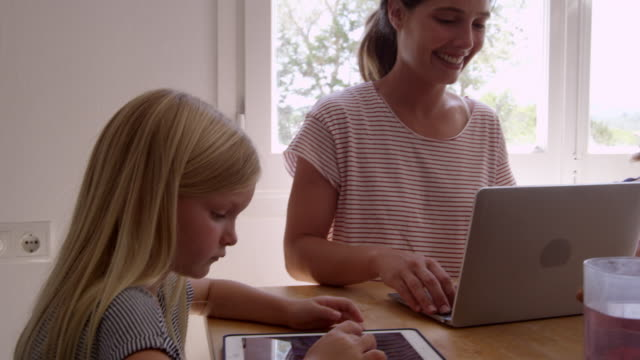 Dad cooking and mum with kids at the kitchen table, shot on R3D video