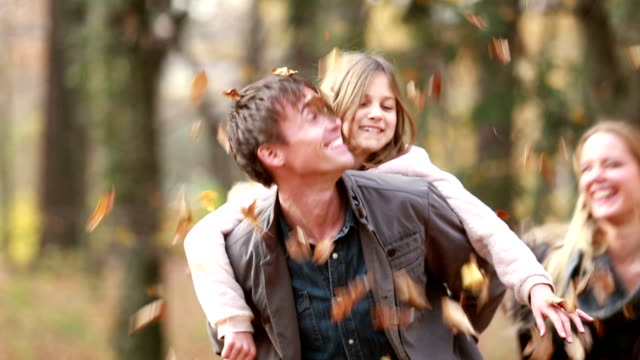 Dad giving daughter piggyback ride, mom throwing leaves at them in park video