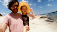 Dad having fun with his daughter at a Beach video
