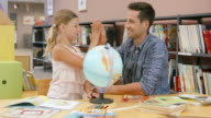 DS Dad helping her daughter learn with a globe in the library video