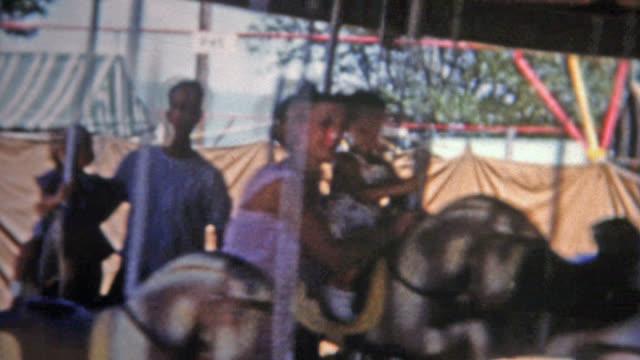 DENVER, COLORADO 1952: Dad holding daughter on horse carousel amusement ride. video