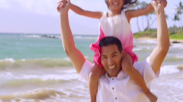 Dad jumps up and down with daughter on shoulders video