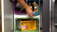 Dad, Mom And Toddler Recycling Waste At Home. Close-Up Of Hands. Slow Motion video